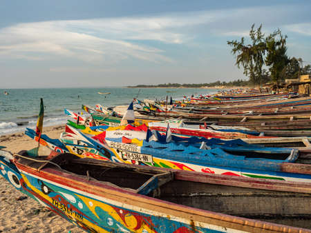 Nianing, Senegal - January 24, 2019: Colorful wooden fisher boats standing on the sandy beach in Senegal. Africa