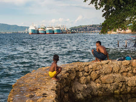 Ambon, Indonesia - February 2018: Many children play and swim in the bathing area at the city beach in the coastal town of Ambon. Ambon Island, Maluku Archipelago, (Moluccas) Indonesia. Asia