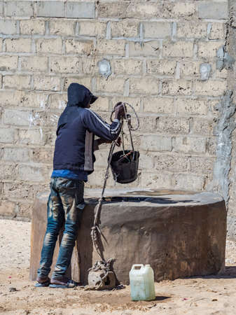 Senegal, Africa - January 2019: A young boy draws water from a well in an African village. 新闻类图片