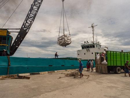 Seram Island, Indonesia - February 2018: Unloading a cargo boat in the port of Seram Island. Maluku archipelago. Maluku, Indonesia, Asia