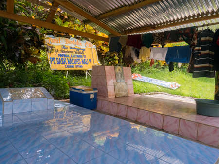 Ambon, Maluku, Indonesia - February 11, 2018: The colorful graves of a family members in the yard next to the house on Ambon Island, 新闻类图片