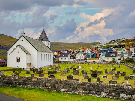 Eiði, Ejde, (Oat), Faroe Islands - Sep, 2020: Small church (Eiðis kirkja) and cemetery with the view on village. Island Eysturoy, Denmark