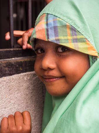 Pasar Kecamatan Pasanea, Indonesia - Feb, 2018: Portrait of a little Muslim girl in traditional dress, Seram Island, Indonesia, Asia