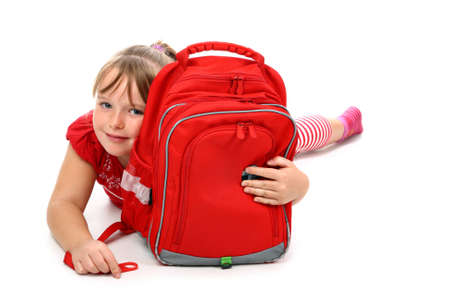 sac d ecole: Happy girl lying on floor hugging red school bag smiling isolated on white