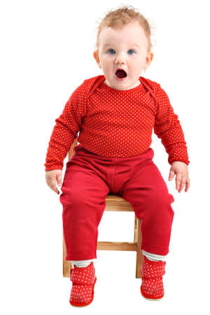 surprised baby: Shocked and startled baby girl dressed in red looking at camera isolated on white