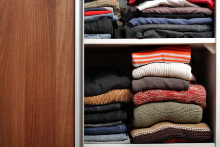 brown clothes: Open wardrobe with lots of folded clothes