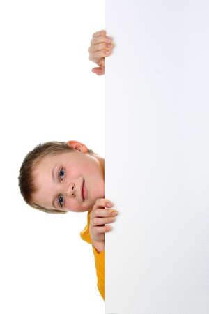 Pequeño niño mira de billboard en blanco con su cabeza inclinada hacia el lado aislado en blanco