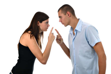 each other: Young couple pointing fingers at each other isolated on white