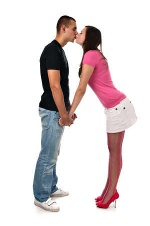 Young girl kisses her boyfriend while holding his hands isolated on white photo