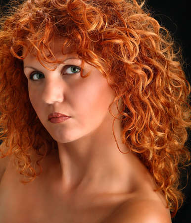 red head: Portrait of beautiful redhead woman with rich curly hair looking at camera