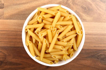 penne: Top view of dry penne rigate in white ceramic bowl on wooden floor