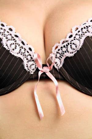 tetas: Pechos femeninos en un sujetador negro con un lazo rosado luz