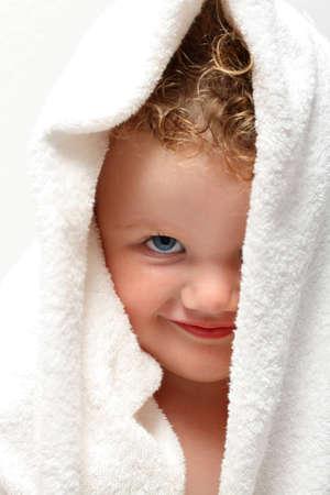 blonde yeux bleus: Baby girl mignon souriant sous une serviette blanche avec un ?il couvert
