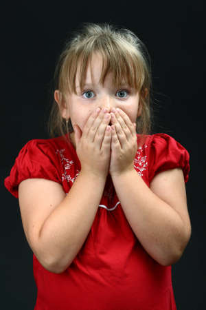 Terrified small girl holding her mouth photo