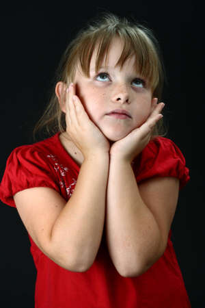 child praying: Small girl holding her cheeks with her hands on black Stock Photo