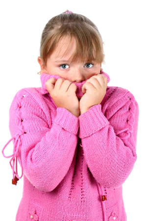 feels: Small girl in pink sweater feeling cold embracing herself looking at camera isolated on white