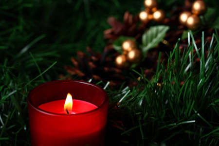 blase: Burning candle in front of cones placed on green fir with copy space Stock Photo