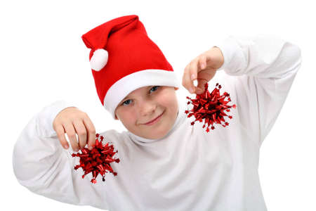 Small boy in Santas red hat holding Christmas decorations isolated on white photo