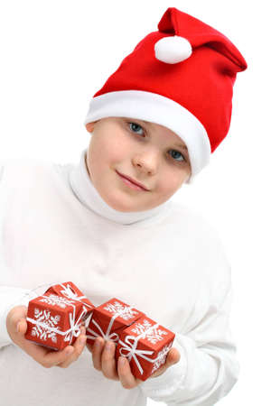 Small boy in Santas red hat holding Christmas presents isolated on white photo