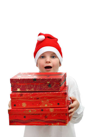 Small boy in Santas red hat carrying three presents isolated on white photo