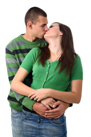 young couple hugging kissing: Young boy kisses and hugs his girlfriend isolated on white