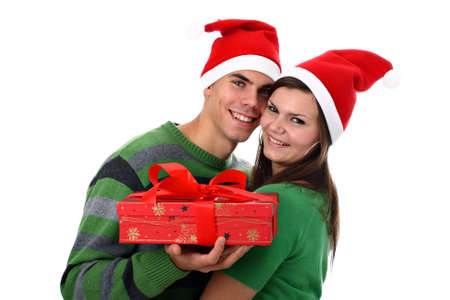 Young couple wearing Santas hats with Christmas present isolated on white photo