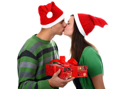 Kissing young couple wearing Santa's hats with Christmas present isolated on white Stock Photo - 10615772