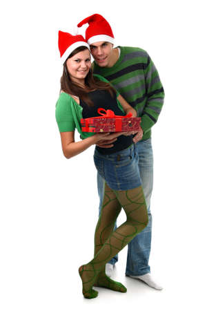 carrying girlfriend: Young couple wearing Santas hats with Christmas present isolated on white