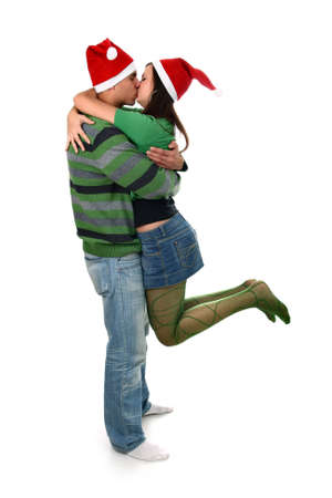 Young woman hanging on her boyfriend kissing him in Santas hats isolated on white photo