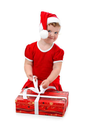 Baby girl in Santas hat unpacking her Christmas present isolated on white photo