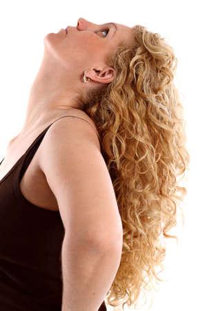 plan éloigné: Portrait d'une jeune femme avec de longs cheveux bouclés blonds levant les yeux, sur fond blanc.