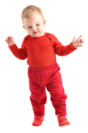 Baby girl dressed in red learning to walk isolated on white photo