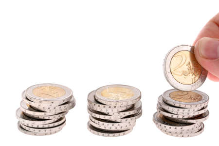 accrue: Hand puts a two-eur coin on third coin column isolated on white background
