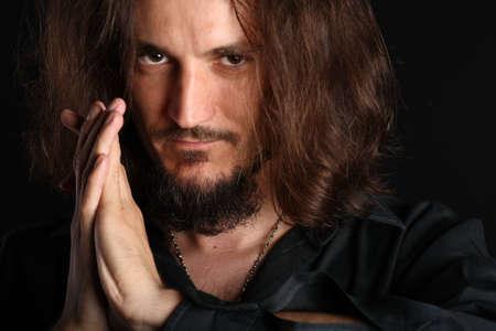 mann mit langen haaren: Junger Mann beten und Blick in die Kamera isoliert auf schwarzem Hintergrund