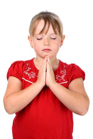 niño orando: Niña pequeña con las manos apretadas y los ojos cerrados oración aislado en blanco