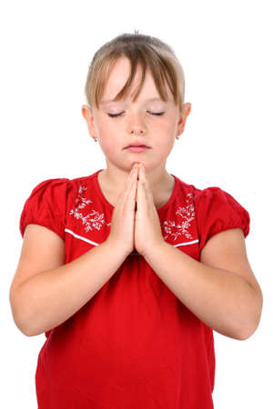 Small girl with clasped hands and eyes closed praying isolated on white photo