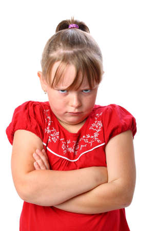 Angry little girl with arms crossed isolated on white photo