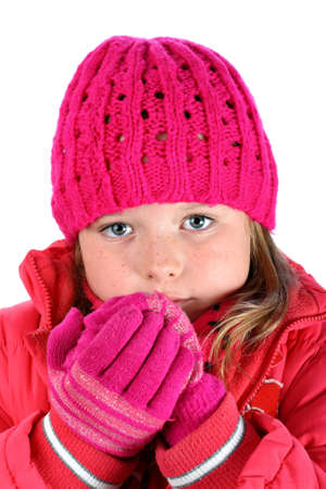Small girl in pink sweater feeling cold breathing on her hands isolated on white photo