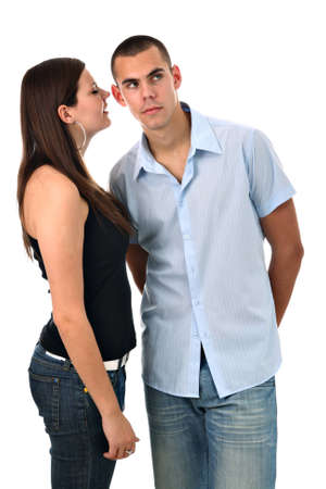 Girl whispers into her boyfriend's ear isolated on white photo