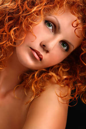 red head girl: Portrait of beautiful redhead woman with rich curly hair looking at camera