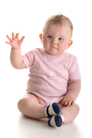 Sweet baby girl sitting and waving arm isolated with shadow photo