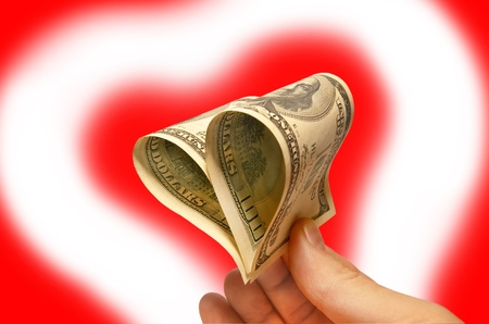 Shape of heart from hundred dollars at red background photo