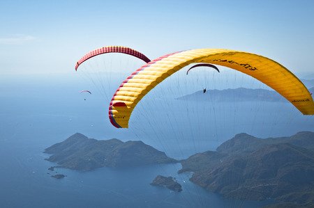 oludeniz: Fethiye, Turkey - September 6, 2013: Paragliding at Fethiye Oludeniz. Paragliding is a free flying sport where the pilot launches themselves by foot.