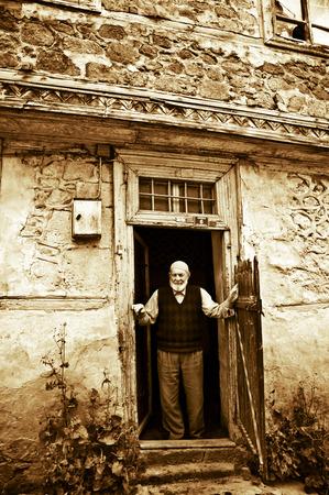 old man standing: Erzurum, Turkey - August 13, 2013: Old man standing in the entrance door of a house in Erzurum-Turkey