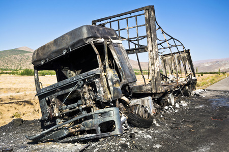 quemado: Quemado camión en una carretera.