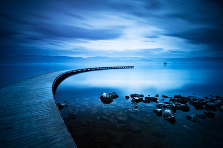 Blue sea and curve jetty , long exposure photography. Foto de archivo