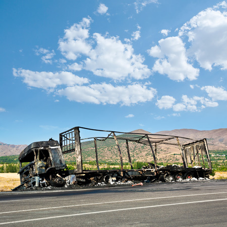 Burned truck waiting on road. Stock Photo