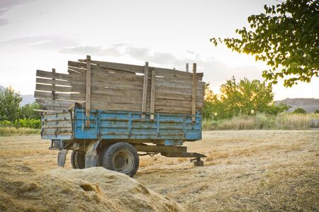 Tractor trailer on straw at sunset , horizontal photo.