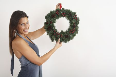 Woman holding up a Christmas wreath Stock Photo - 2219943