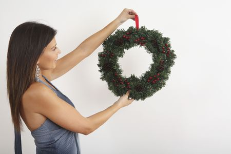 Woman holding up a Christmas wreath Stock Photo - 2219939